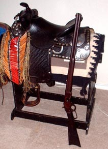 Photo of old west saddle, Winchester 73 and Native American Breastplate
